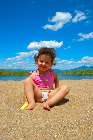 Beautifull baby girl on the beach with curious expresion on her face Standard-Bild