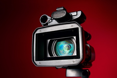 Professional video camera on a red background