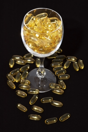nutritional supplement: Glass full of nutritional supplement pills on black background. Stock Photo