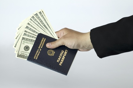 Close-up of woman hand in a suit with passport and dollars. photo