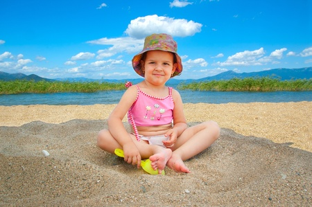 Little girl playing on beach under a big umbrella Stock Photo - 10313866