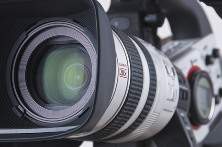 Super close up of Professional Video Camera. The Focus is on the lens and the front part