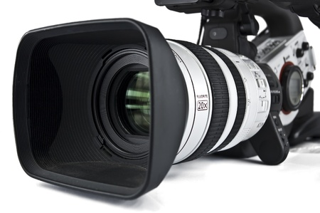 video camera: Professional video camera pointing to camera left. Lens hood and front of lens are in focus, the rest is soft