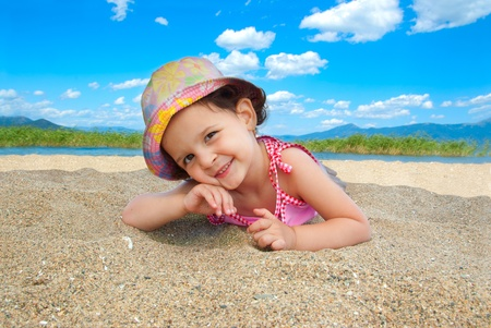 Young girl at the beach playing in the sand