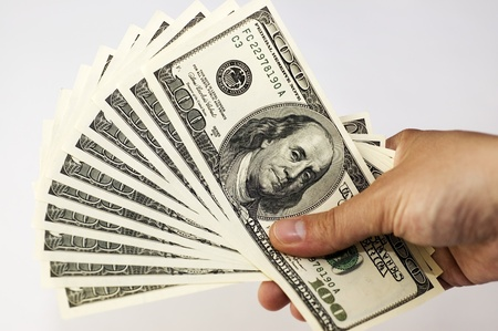 Close-up of man hand holding  a pile of 100 dollars isolated on white background. Standard-Bild