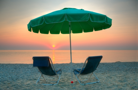 Chairs and umbrella on a beach at sunrise