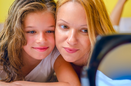 smiling mother and daughter relaxing in bed and looking into mirror