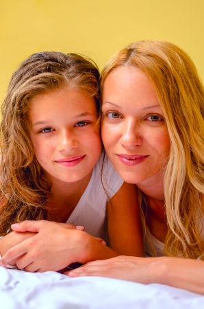 Happy mother and daughter laying in bed ( yellow background ) Stock Photo