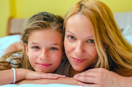 Close up of a young girl and her mother laying on bed