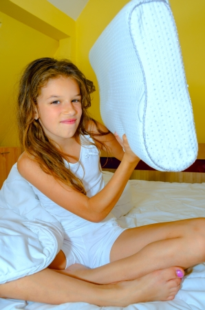 Young girl playing with pillow Stock Photo