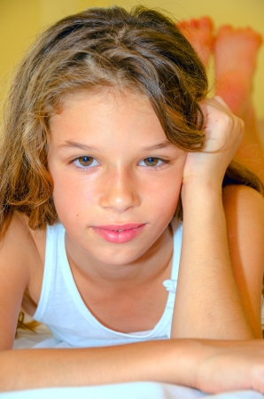 little girl laying on bed and looking at the camera Stock Photo
