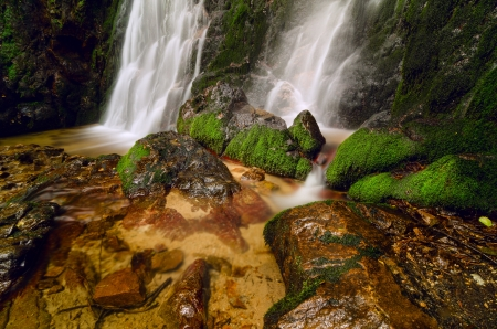 Waterfall spilling into a pool with mossy rocks Stock Photo