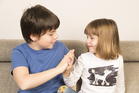 clasping: Glad children clasping hands on a sofa