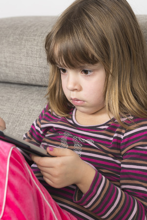 Little girl playing with a digital tablet at home on a sofa photo