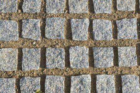 Miscellaneous cobblestone squares are placed symmetrically on a sandy floor photo
