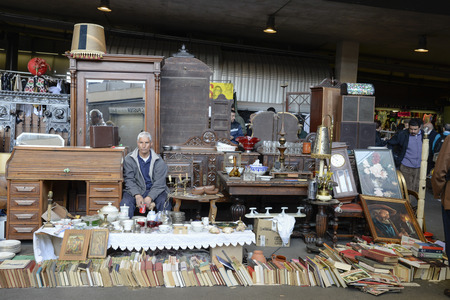 resale: Barcelona, Spain - March 12, 2014  Seller at his post of objects and furniture resale in the most famous flea market in Barcelona, also known as Els Encants or Els Encants Vells, located in Glories neighborhood  Seller at his post of objects and furniture