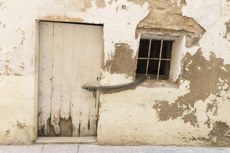 old house wall with white door and window together with a chain and padlock photo