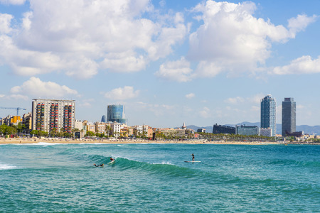 Barcelona, Spain - May 16, 2014  Beautiful summer morning on Barceloneta beach In the image appear three surfers  The background looks a skyline of Barcelona View of Barcelona from the beach of Barceloneta with surfers Editorial