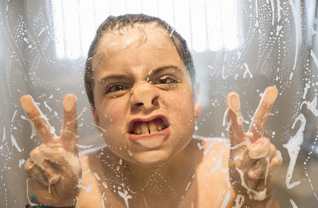 Young  boy  9-10   playing in the shower pressing her face against the glass making the victory sign with hands