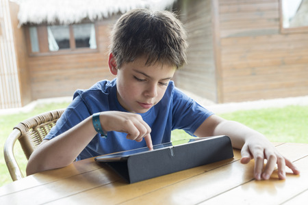 10 11 years: Young boy playing with a tablet digital sitting on a terrace