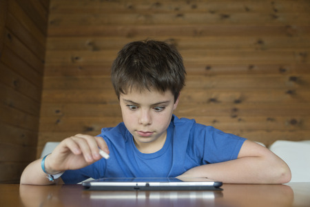 Young boy playing with a tablet digital sitting on a sofa photo