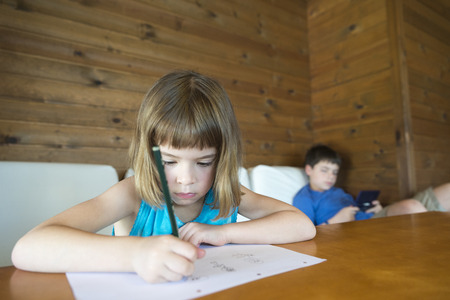 The girl draws while the child plays video games stretched on the sofa photo
