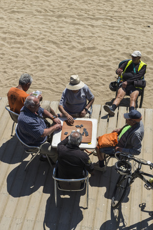 Barcelona, Spain - May 16, 2014  Zenith angle of senior people playing dominoes in the Barceloneta beach while their friends watch the game having a beer  Others take the sun or read  Senior people playing dominoes in the Barceloneta beach, Barcelona