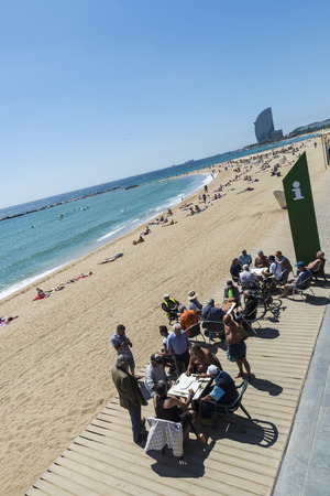 Barcelona, Spain - May 16, 2014  Panoramic of senior people playing dominoes in the Barceloneta beach while their friends watch the game having a beer  Others take the sun or read  In the background appears people sunbathing on the beach and skyline of Ba