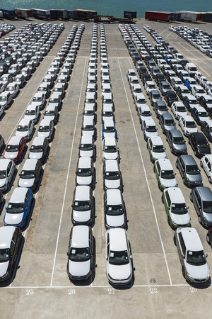 Barcelona, Spain - May 23, 2014  New cars parked in a row in the port of Barcelona  They are waiting to be shipped  In the background is parked trucks and containers New cars parked in a row in the port of Barcelona