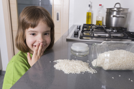 little accident in the kitchen  Surprised little girl to fall a glass container filled with rice Standard-Bild