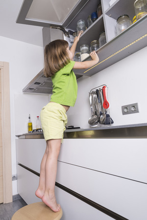 Little girl on a chair to reach higher to get chocolate in the kitchen Stock Photo