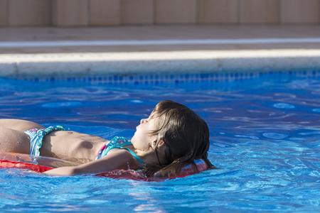 어린 소녀: Little girl on an inflatable mattress in a swimming pool 스톡 사진