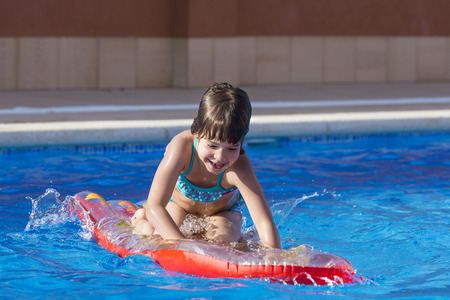 Little girl on an inflatable mattress in a swimming pool  photo