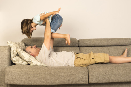 man lying on sofa and lifting up his daughter photo