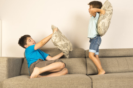 pillow fight: Children fighting together with pillows on sofa at home