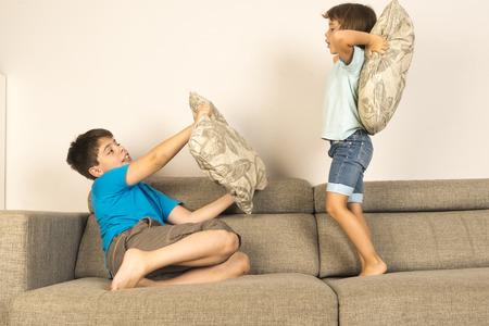peleando: Ni�os luchando juntos con almohadas en el sof� en casa