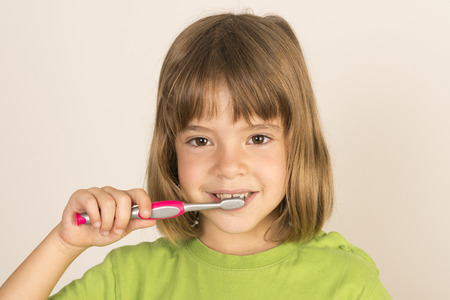 Portrait of a little girl brushing his teeth  photo
