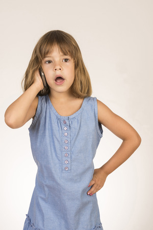 Little girl standing talking on cellphone with white background photo