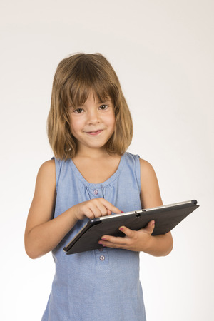 Little girl playing with a digital tablet with white background photo