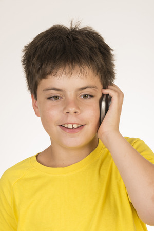 Young boy talking with mobile isolated on white background photo