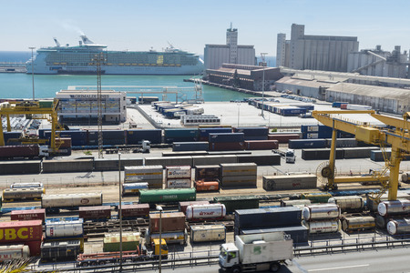 vats: Barcelona, Spain - May 14, 2014: Overview of Container Terminal in the port of Barcelona where there are all kinds of containers, vats and new cars for export. In the background is moored on Liberty of the Seas cruise, cruise the second worlds largest lu