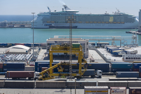 Barcelona, Spain - May 14, 2014: Overview of Container Terminal in the port of Barcelona where there are all kinds of containers, vats and new cars for export. In the background is moored on Liberty of the Seas cruise, cruise the second worlds largest lu