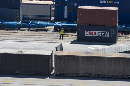 vats: Barcelona, Spain - May 14, 2014: Overview of Container Terminal in the port of Barcelona where there are all kinds of containers and vats. In the picture, a worker directs and organizes container traffic. Container Terminal in the port of Barcelona