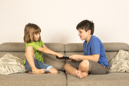 Kids arguing for playing with a digital tablet on a sofa