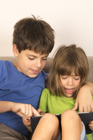 Children playing with a digital tablet on the sofa photo