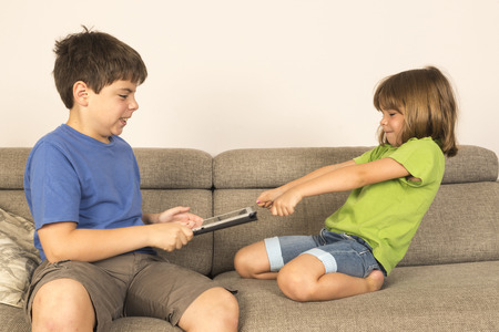 Kids arguing for playing with a digital tablet on a sofa   photo