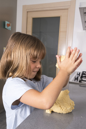 Little girl making cookie dough at home photo