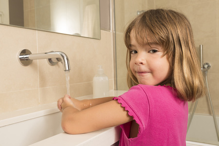 Closeup of child washing hands under the tap photo