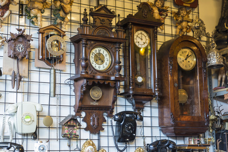 Barcelona, Spain - June 18, 2014  Objects used, clocks, phones and ornaments on a market stall in the most famous flea market in Barcelona, also known as Els Encants or Els Encants Vells, located in Glories neighborhood Objects used, furniture, artwork an