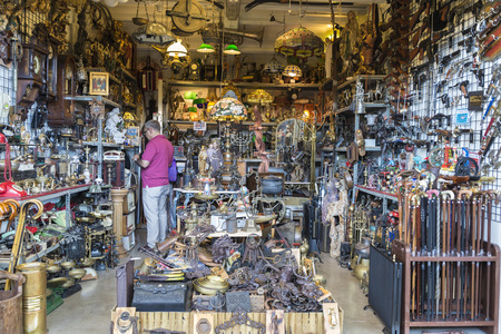 Barcelona, Spain - June 18, 2014   Seller at his post of objects, antiques, old weapons, and furniture resale in the most famous flea market in Barcelona, also known as Els Encants or Els Encants Vells, located in Glories neighborhood  Seller at his post